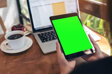 Mockup image of hands holding black tablet pc with blank green screen , laptop , coffee cup and cake on wooden table in cafe