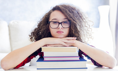 Teen girl resting on books