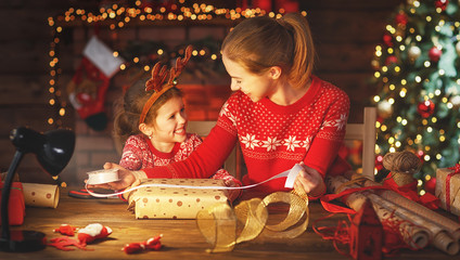 happy family mother and child pack Christmas gifts.
