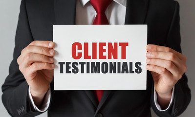 Businessman holding a card with text Client Testimonials