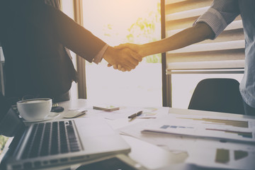 Close-up of two business people shaking hands during a meeting in the office,