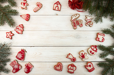 Overhead of Christmas New Year holiday background. Red gingerbread cookies and fir branch tree on white wooden table. Top view.