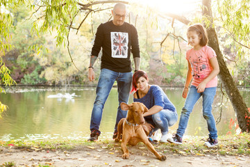Family of father, mother and daughter on the riverside playing with their dog. Animal lovers