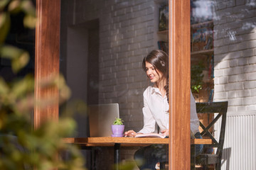 Young attractive woman sitting at the cafe working on her laptop smiling happily relax weekend lifestyle leisure happiness technology internet online browsing studying educational concept.