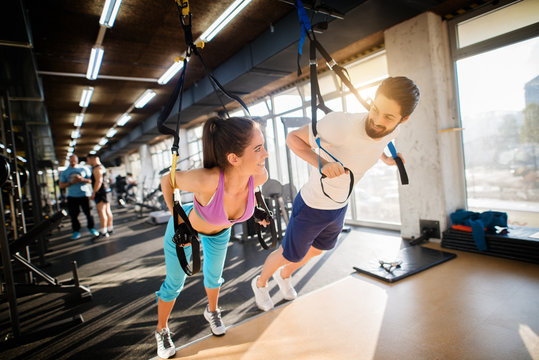 Young handsome fitness couple flirting while exercising with TRX in the gym.
