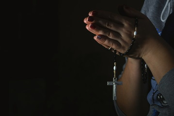 Woman hands holding rosary on black background