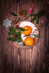 Tangerines, candy canes and other Christmas and New Year symbols on a wooden background. Top view, free space for text