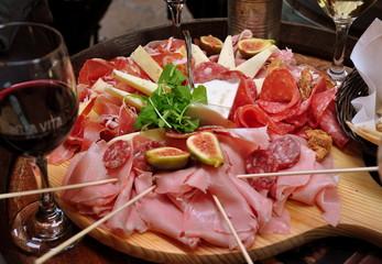 Rundes Holzbrett mit leckerem Schinken, Salami und Käse sowie Spießchen und einem Glas Rotwein im Vordergrund