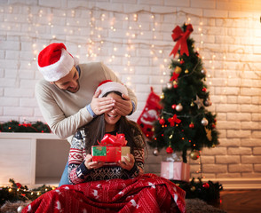 Young handsome man with Santa hat holding eye closed of his girlfriend while she sitting on a carpet with a present in hands for Christmas holidays.