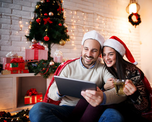 Cute smiling couple sitting on a carpet with Santa hats hugged while looking on a tablet and drinking a tea for Chrismas holidays.