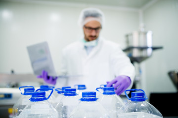 A lot of bottles with water in front of a blured scientist in the laboratory.