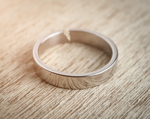 Cracked silver wedding ring on wood,Divorce and ending relationship concept