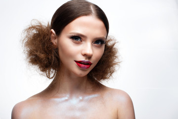 Young girl with creative bright makeup and shining skin. Beautiful model with a hairdo, arrows on eyes and red lips. Beauty of the face. Photo is taken in the studio. White isolated background.