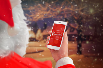 Santa Claus holding smart phone with Merry Christmas massage. Winter and snow outdoor in background.
