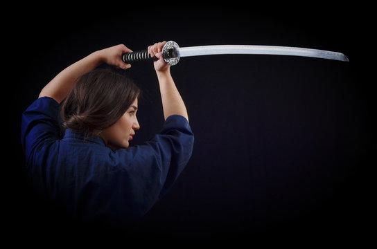 brunette girl in a kimono holding a sword