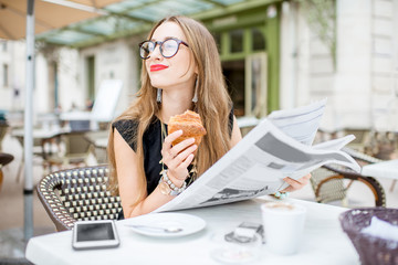 Young woman reading newspaper during a breakfast with croissant sitting outdoors at the typical french cafe terrace in France