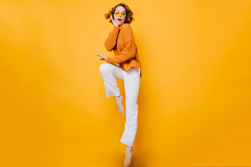 Amazing short-haired woman in trendy sweater standing on one leg and propping face with hand. Indoor full-length portrait of enthusiastic barefooted girl wears white pants. Wall mural