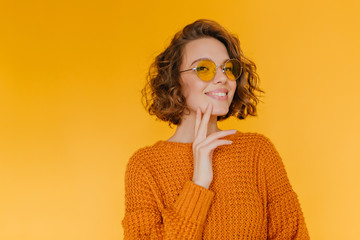 Cheerful short-haired girl in trendy glasses posing with pleasure in new knitted attire. Indoor portrait of pleased curly young woman standing in front of yellow wall.