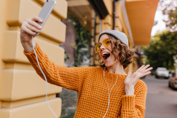 Gorgeous female model in gray hat fooling around on the street while making selfie. Fashionable girl in yellow sweater listening music in earphones and taking picture of herself with smile.