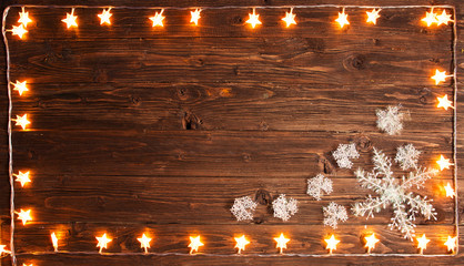 Christmas warm gold garland lights with snowflakes on wooden rustic background. Christmas or New Year concept