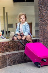Little kid girl with travel suitcase outdoors.