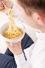 Young man is eating instant noodles from the white bowl