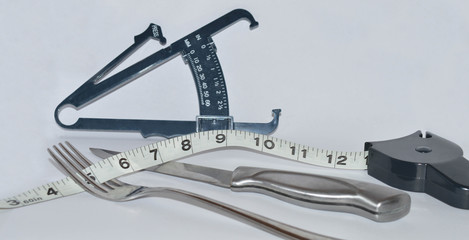 A fork and knife by body measuring tools to represent dieting