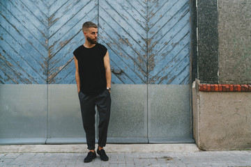 Full length portrait of a handsome bearded man dressed in fashionable clothes standing on a street against the retro light blue wooden gates. Handsome hipster guy posing in a blank black t-shirt.