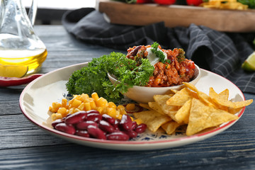 Bowl with chili con carne and nacho chips on plate