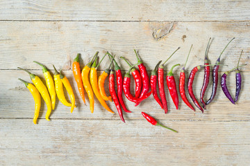 Colorful chili peppers in color order on wooden table, top view.