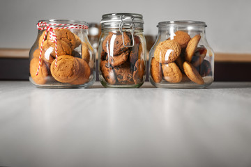 Glass jars with delicious oatmeal cookies on wooden table