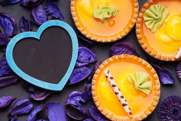 Orange cake baskets and heart shape on a flower petals background