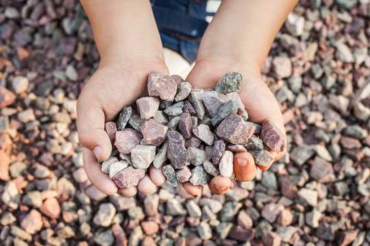 Child holding small colorful stones in little hands. Concept of game money, valuable resource