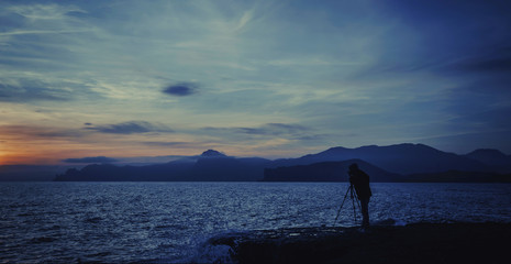 Silhouette of photographer against the blue sea at sunset