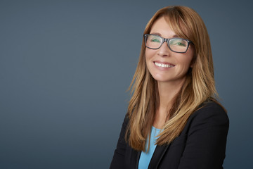 Attractive middle aged businesswoman against grey background.