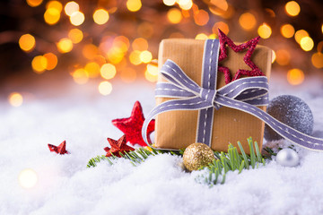 Christmas gift in snow landscape with bokeh background