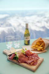 Cutted delicacies with french fries and wine on table in cafe of mountain's resort