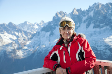 a middle-aged woman in a ski mask in winter mountains on Sunny day