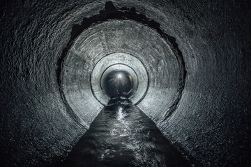 Underground river flowing in round concrete sewer tunnel. Sewage collector
