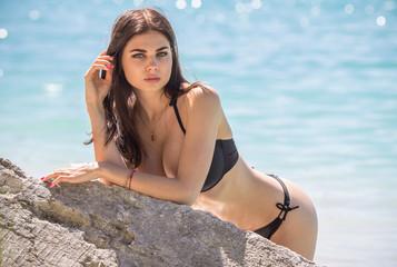 Sexy woman in bikini on sea background