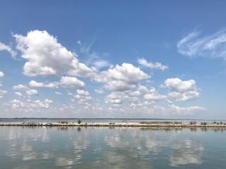летний морской пейзаж. белые облака отражаются в море