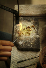 Balinese Jewelry Maker in Amlapura Market. A jeweler uses a torch to construct a necklace and ring in the public market in eastern Bali, Indonesia.