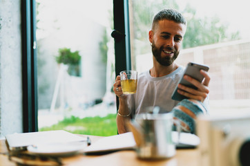 Cheerful casually dressed bearded male freelancer checking email on a mobile phone waiting for answer from the clients. Smiling hipster guy surfing the web on smartphone in a coffee shop.