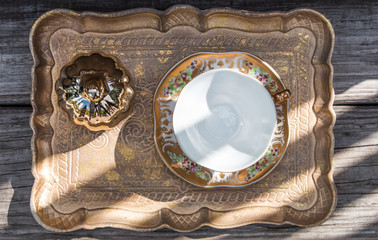 Golden table decoration idea - tray, mirror in gold frame, porcelain tea cup, jewelry box