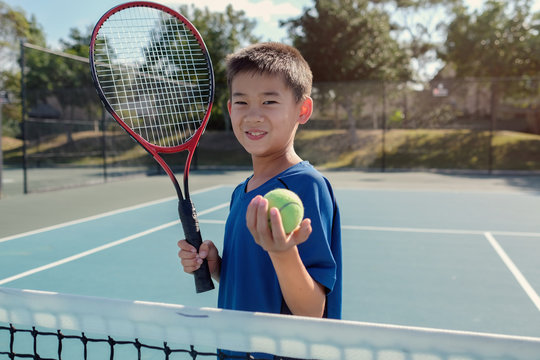 Young tween multiethnic Asian boy tennis player on outdoor blue court