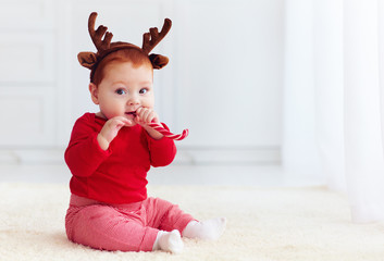 cute little redhead baby boy with reindeer band tasting christmas sweet treats, sitting on the floor at home