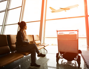 single woman sitting in airport terminal and passanger plane flying outdoor for traveling theme