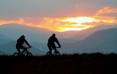 Mountain bikers on a trail at sunset Wall mural