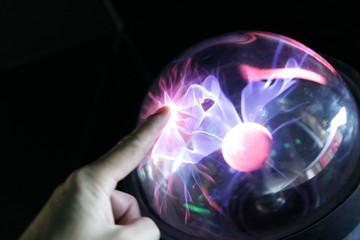 hand touching plasma globe