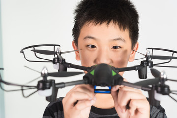 Asian boy holding drone or quadcopter in hand, on white background.